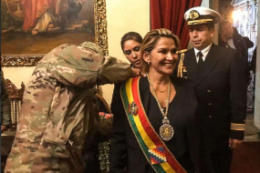 A military person putting the presidential scarf on senator Jeanine Añez
